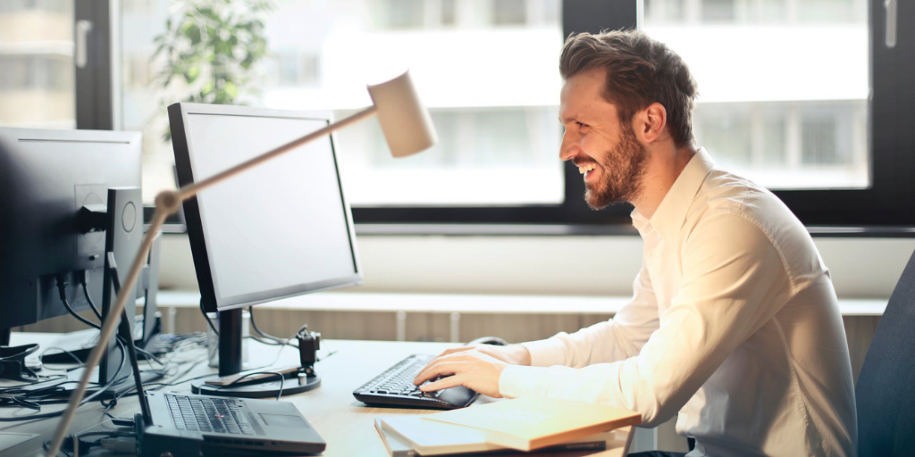 Man sitting at computer smiling